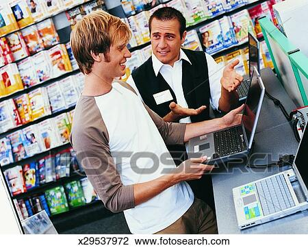 Stock Photo of Shop Assistant Giving a Customer Advice About a - shop assistan