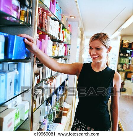 Stock Photography of Young, Smiling Shop Assistant Reaching for