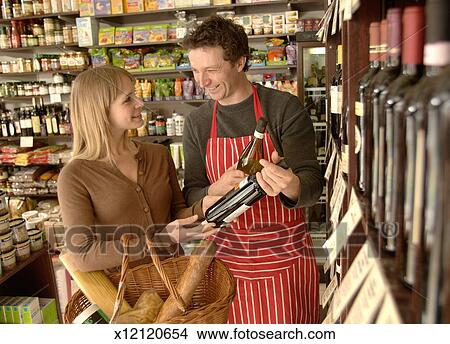 Male shop assistant helping female customer choose wine Stock Photo