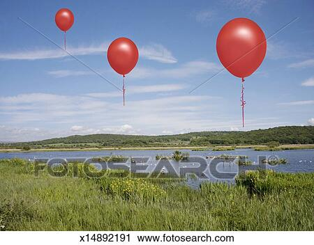 Stock Photography of Red balloons floating over wet lands x14892191
