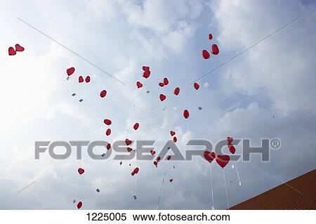 Stock Image of Many red heart shaped helium balloons floating up