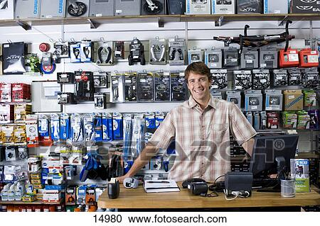 Stock Photography of Shop assistant behind counter, smiling - shop assistan