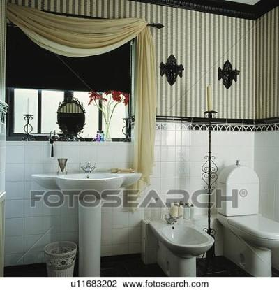 Stock Photo of Black+white striped wallpaper above white tiled wall in bathroom with cream drape ...