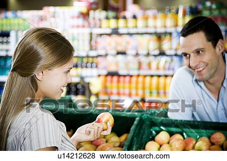 Pictures of Supermarket shop assistant flirting with a customer - shop assistan