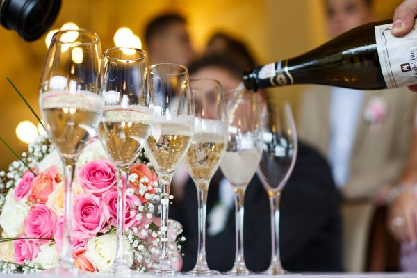 Man pours champagne in the glasses standing before a wedding bouquet on the table