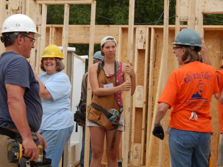 Jasmine Luedi, 16, is carrying her late grandfather Millard Fuller's hammer on the job site this week.