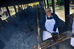 Ernest Hargrave begins to season shad on a plank near the fire during the 66th annual Shad Planking Wednesday afternoon in Wakefield.
