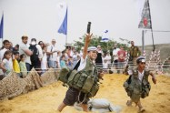 An Israeli boy dresses wearing a military vest throws a mock granade during a traditional military weapon display to mark the 66th anniversary of Israel's Independence at the West Bank settlement of Efrat on May 6, 2014 near the biblical city of Bethlehem. AFP PHOTO/GALI TIBBONGALI TIBBON/AFP/Getty