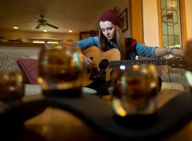 Bria Kelly plays guitar in the living room of her Smithfield home on Wednesday afternoon.