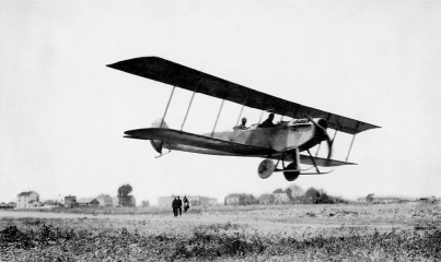 "The Curtiss JN4 ""Jenny"" ranked among the most famous and well-recognized early airplanes, especially after it became the aircraft of choice for dare-devil pilots performing in barnstorming demonstrations during the 1920s. This 1916 photo shows it flying over the Curtiss Flying School airstrip in Newport News with spectators and houses along Ivy Avenue in the background. (Courtesy of Kurt P. Wheaton)"