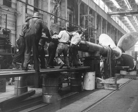 SS America -- This 1939 photo shows Newport News Shipbuilding workers assembling one of the SS America's 32-ton propeller shafts to a 22-ton propeller by ramming it into place with a 4,800-pound battering ram. Despite the immensity of the physical forces involved, the work resulted in fits as exact as one-thousandth of an inch.