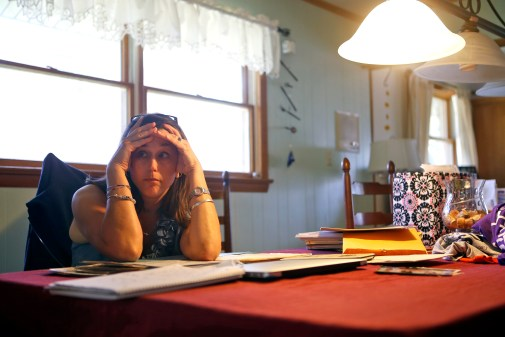 Patti Minium Moonis sits amongst her medical records while inside her home during a Friday afternoon in August. Patti was diagnosed with chronic myelogenous leukemia in October in 2013. Patti was adopted when she was three weeks old and only recently found her biological mother.