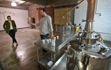 Marketer Kara King and distiller Owen King stand inside the distilling room of Ironclad Distillery in downtown Newport News. (Joe Fudge)