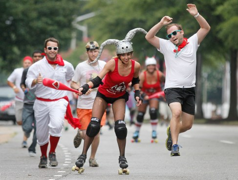 Christian Quirk jumps in the air as he is hit by Dominion Derby Girl Christina Bieg during the annual Rolling of the Bulls in Hampton Saturday.