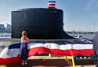 Anya Eichenlaub looks at the submarine USS John Warner during the commissioning ceremony at Naval Station Norfolk Saturday morning August 1, 2015. Anya's father, Mark Eichenlaub, is Assistant Navigator for the SSN-785.