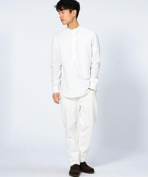 バンドカラーシャツを全身白で着こなした男性