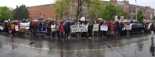 Image of Parkdale Organize members outside the Toronto Food Terminal holding umbrellas in the rain. Signs read Parkdale Fights Back