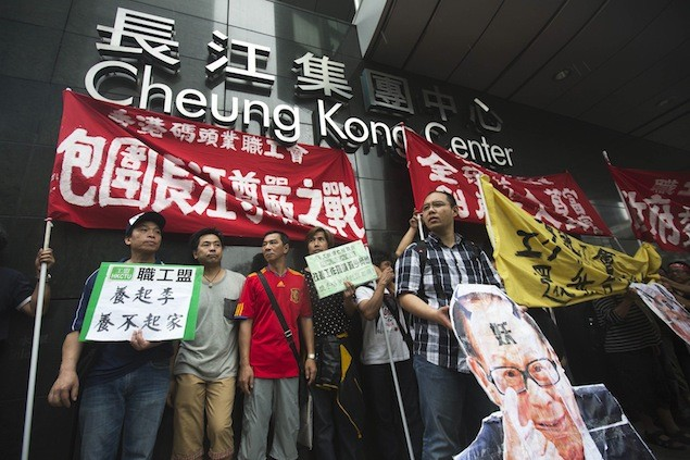 Dock workers march with a defaced picture of Hong Kong's tycoon Li Ka-shing during a strike outside Cheung Kong Center in Hong Kong's financial Central District April 17, 2013. REUTERS/Tyrone Siu