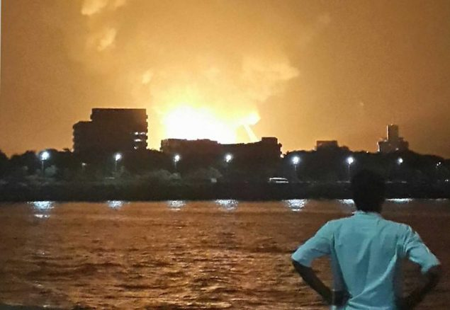 A man watches Indian Navy submarine INS Sindhurakshak on fire in Mumbai late August 13, 2013. Picture taken late August 13, 2013. REUTERS/Vikalp Shah
