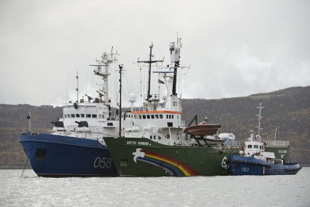 "Greenpeace ship ""Arctic Sunrise"" (C) is seen anchored outside the Arctic port city of Murmansk, on the day when members of Russian Investigation Committee conducted an inspection onboard the Greenpeace ship, in this September 28, 2013 handout provided by Greenpeace. A Russian court ordered 20 Greenpeace activists from around the world to be held in custody for two months pending further investigation over a protest against offshore oil drilling in the Arctic, drawing condemnation and a vow to appeal. In proceedings that Greenpeace said evoked Soviet-era scare tactics, activists from a ship used in the protest at an oil rig were led to court in the port of Murmansk in handcuffs and held in cages for a series of hearings that ended early on September 27. Picture taken September 28, 2013. Mandatory Credit. REUTERS/Dmitri Sharomov/Greenpeace/Handout via Reuters"