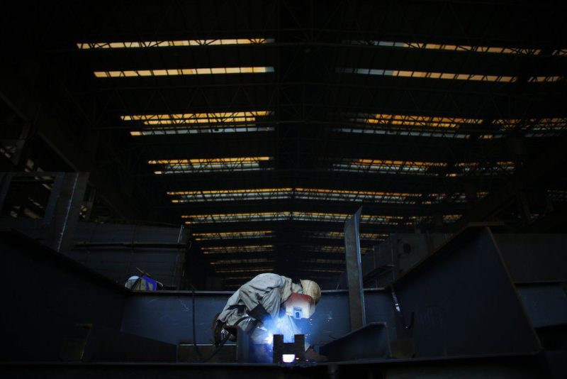 A labourer works on a section of a vessel which is under construction at the Waigaoqiao shipyard in Shanghai November 5, 2013. REUTERS/Carlos Barria