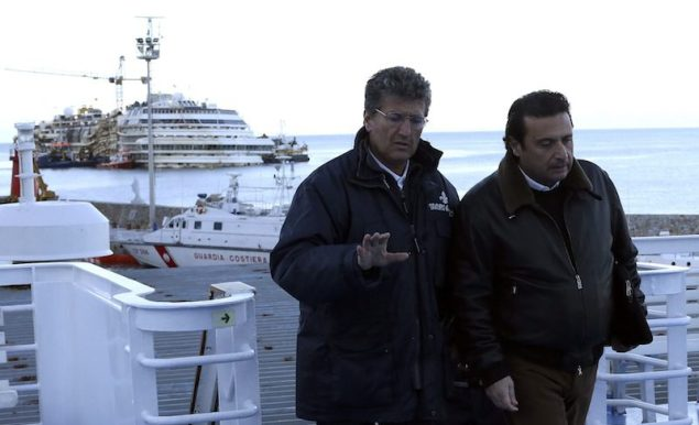 Francesco Schettino (R), the captain of the Costa Concordia cruise liner (pictured at rear), boards a ferry as he leaves Giglio harbour February 27, 2014. REUTERS/Alessandro Bianchi