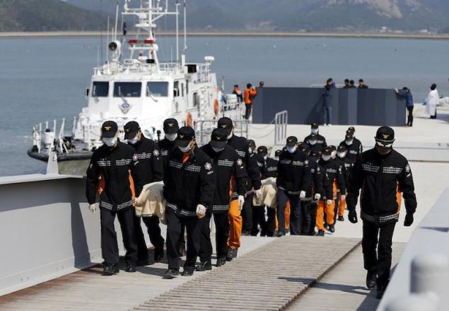 South Korean rescue workers carry the bodies of passengers who were on the capsized passenger ship Sewol which sank in the sea off Jindo, at a port where family members of missing passengers gather in Jindo April 20, 2014. REUTERS/Issei Kato