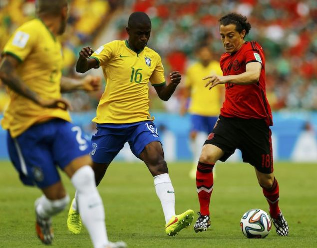 Mexico's Andres Guardado (R) fights for the ball with Brazil's Ramires (C) and Daniel Alves during their 2014 World Cup Group A soccer match at the Castelao arena in Fortaleza June 17, 2014. REUTERS/Marcelo Del Pozo
