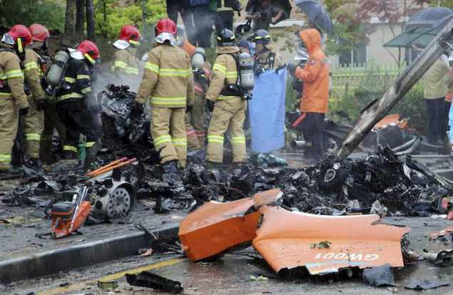 Firefighters inspect the wreckage of a helicopter which crashed near an apartment complex in Gwangju July 17, 2014. REUTERS/Park Cheol-hong/Yonhap