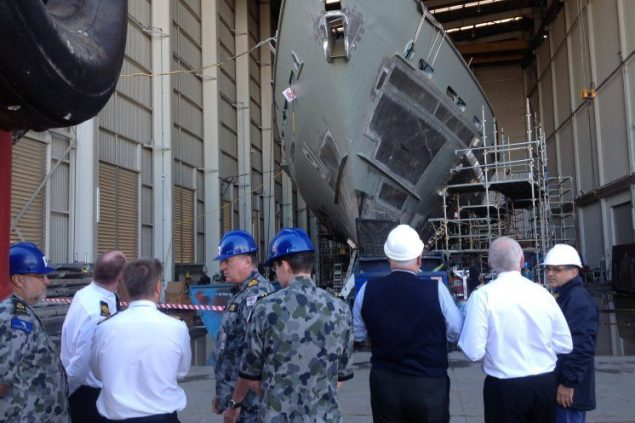Chief of Navy, Vice Admiral Tim Barrett (third from left) inspects the hull of the fire damaged Armidale Class Patrol Boat HMAS Bundaberg at a Brisbane dockyard. Photo courtesy Royal Australian Navy