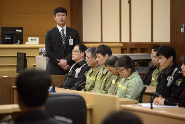 Sewol ferry captain Lee Joon-seok (man in green, wearing glasses) sits with crew members at the start of the verdict proceedings in a court room in Gwangju November 11, 2014. REUTERS/Ed Jones/Pool