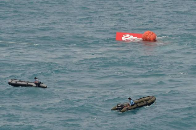 Part of the tail of AirAsia QZ8501 floats on the surface after being lifted as Indonesian navy divers conduct search operations for the black box flight recorders and passengers and crew of the aircraft, in the Java Sea January 10, 2015. REUTERS/Adek Berry/Pool