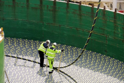 Workers guide the loading of miles of subsea power cables onto the spool of Skagerrak.  Image courtesy of Nexans