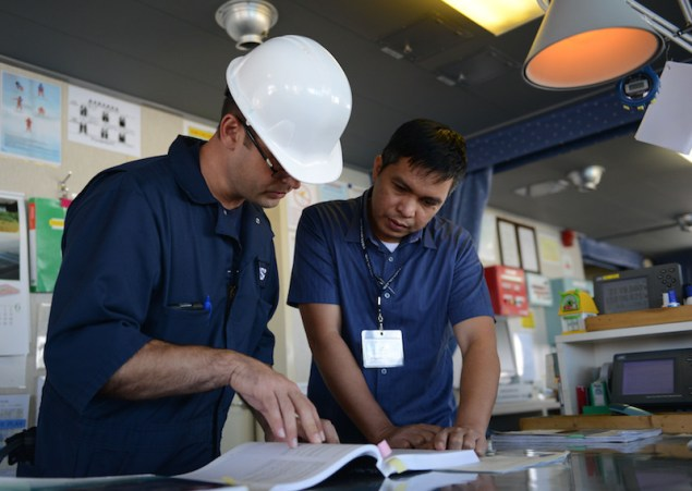 Lt.j.g. Nathan Clinger, a port state control officer at Coast Guard Sector Honolulu Prevention, checks a manual with the ship's captain aboard the 600-foot Panamanian flagged bulk freight ship, Teizan, at Kalaeloa Barbers Point Harbor, May 19, 2015. Coast Guard crew members conduct inspections to ensure a vessel has a suitable structure, correct documentation, proper working equipment and lifesaving equipment and adequate accommodations. (U.S. Coast Guard photo by Petty Officer 2nd Class Tara Molle)