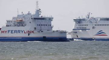 MyFerryLink car and passenger ferries cross outside the harbour in Calais, northern France, June 24, 2015. REUTERS/Christian Hartmann