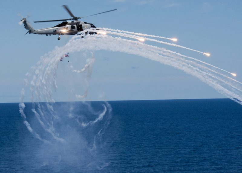 150711-N-ZZ999-532 PACIFIC OCEAN (July 11, 2015) An MH-60R Sea Hawk helicopter attached to the Battle Cats of Helicopter Maritime Strike Squadron (HSM) 73 fires flares near the aircraft carrier USS Carl Vinson (CVN 70) during an air power demonstration. Carl Vinson hosts more than 2,000 family members and friends to demonstrate the ship's capabilities. (U.S. Navy photo by Mass Communication Specialist Seaman Tom Tonthat/Released)
