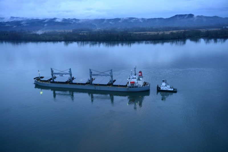 A tug helps stabilize the motor vessel Sparna, a 623-foot Panamanian-flagged bulk carrier, while the Sparna awaits repairs after it sustained damage below the waterline while transiting in the Columbia River near Cathlamet, Wash., March 21, 2016. The Sparna is loaded with grain and was headed west on the Columbia River when the incident occurred. (U.S. Coast Guard photo by Petty Officer 1st Class Levi Read)
