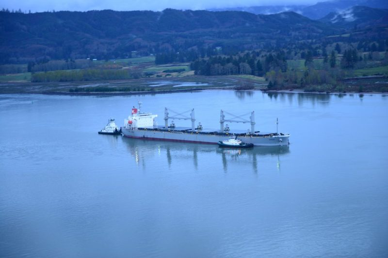 Two tugs assist the motor vessel Sparna, a 623-foot Panamanian-flagged bulk carrier with a load of grain, with maintaining position after the vessel reportedly ran aground in the Columbia River near Cathlamet, Wash., March 21, 2016. A salvage plan will be approved by the Coast Guard before the vessel can be moved from its current location. (U.S. Coast Guard photo by Petty Officer 1st Class Levi Read)