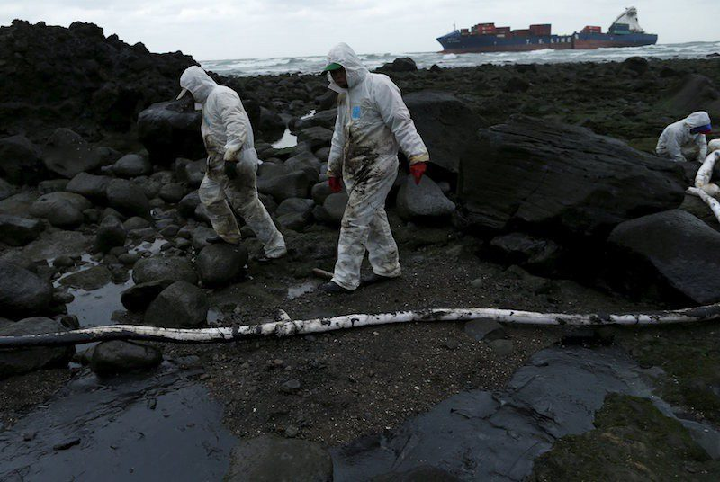 Cleaners walk past protective booms around fuel that leaked from a cargo ship owned by TS Lines Co (in background), off the shores of New Taipei City, Taiwan, March 25, 2016. Photo: REUTERS/Tyrone Siu