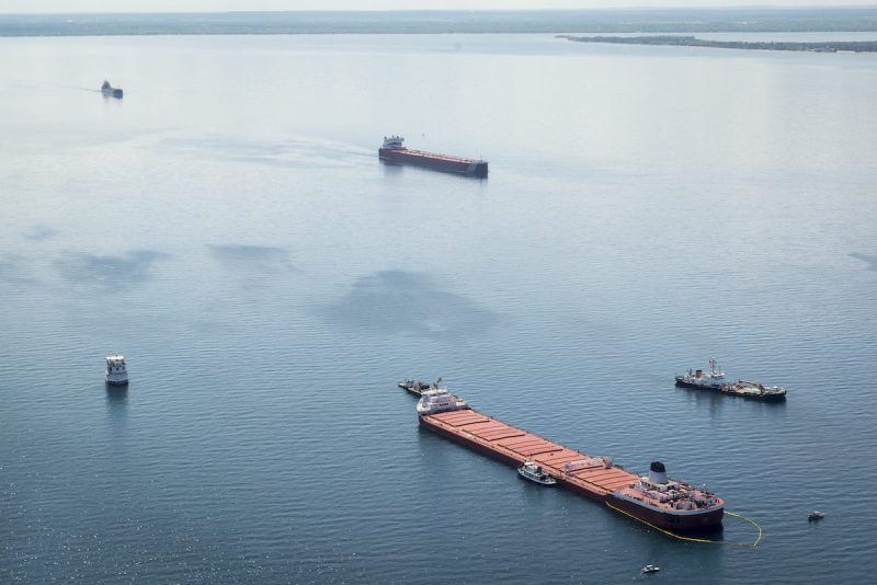 Two freighters transit upbound the Soo Locks past the safety zone established by the U.S. Coast Guard around the motor vessel Roger Blough near Gros Reefs Light, May 30, 2016 in Lake Superior. The safety zone was established after the Blough ran aground on the reef May 27. (U.S. Coast Guard photo by Petty Officer 2nd Class Christopher M. Yaw)