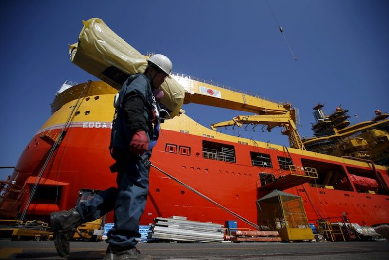 A worker carries construction materials as he walks past a ship which is currently under construction at Hyundai Heavy Industries' Shipyard in Ulsan, South Korea, May 13, 2015. REUTERS/Kim Hong-Ji/File Photo