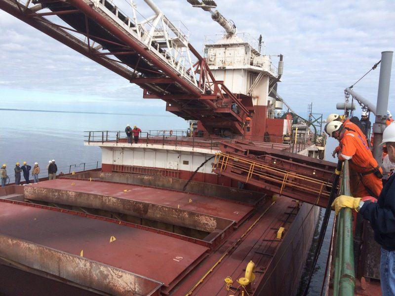 The motor vessel Phillip R. Clarke receives taconite by conveyor belt from the motor vessel Roger Blough that ran aground on May 27, near Gros Cap Reefs Light in Lake Superior, June 3, 2016. The Clarke is scheduled to remove some of the taconite from the Blough in order to lighten the Blough so it can be refloated. (U.S. Coast Guard photo by Petty Officer 2nd Class Kyle Schmidt)