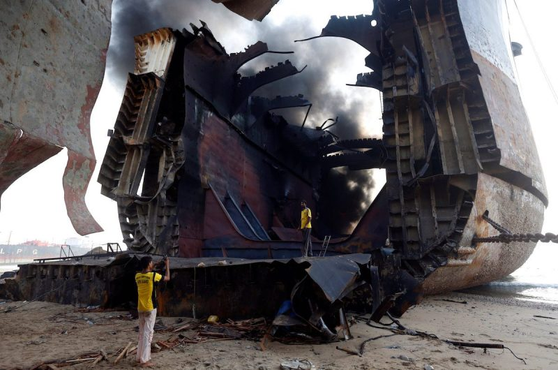 A man takes photo of his colleague with a mobile phone on the burning oil tanker at the ship-breaking yard in Gaddani, Pakistan, November 2, 2016. REUTERS/Akhtar Soomro