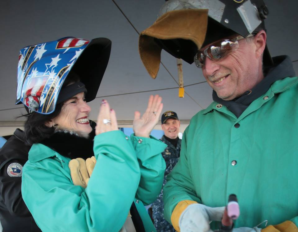 Luci Baines Johnson applauds Timothy Trask, a Bath Iron Works welder, after he helped her authenticate the keel plate of DDG 1002, the future USS Lyndon B. Johnson, January 30, 2017. Photo: Bath Iron Works