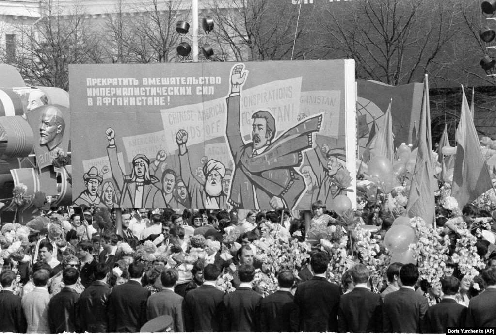 """May Day marchers on Red Square carry a placard demanding """"an end to imperialistic meddling in Afghanistan"""" on May 1, 1980."""