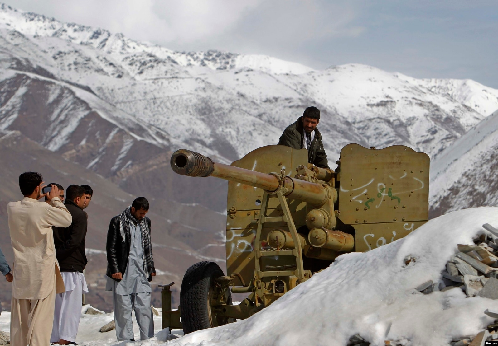 Afghans look at destroyed Soviet artillery at a junkyard in Panjshir Province, north of Kabul, in 2014.