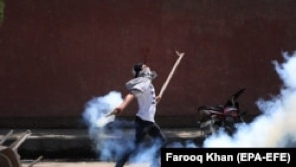 A Kashmiri student throws back a tear smoke shell at Indian police on May 14.