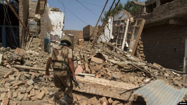 FILE: A Pakistani soldier walks in a house destroyed during a military operation in the of town of Miran Shah, North Waziristan in July 2014.