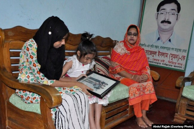 Two daughters of Sajedal Islam Sumon are looking at their father's years old photo. Sumon's wife (in orange clothing) is sitting at one corner in her house in Dhaka (28 NOV 2017).