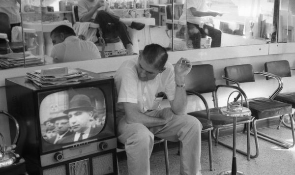 The final episode of the first series of The Secret Life of Machines examines the development of television, much like the set this man is watching at a barber shop in Tallahassee, FL, USA. (Collection of the State Library and Archives of Florida - no known copyright restrictions).